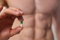Athlete bodybuilder takes dope in the form of tablets form of pharma rapid progress in muscle Royalty Free Stock Images
