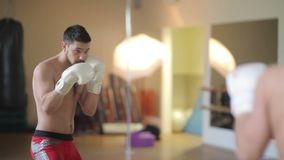 Athlete boxing in front of a mirror stock video footage