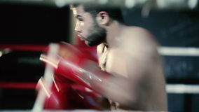 Athlete boxing in the ring. An athlete trains in the boxing gym. The boxer trains a series of blows. Young man shirtless trains in the boxing hall stock video