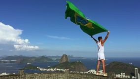 Athlete Brazilian Flag Rio de Janeiro. Athlete in old-fashioned white sports uniform standing with Brazilian flag at city skyline overlook in Rio de Janeiro