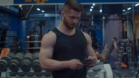 Athlete during the break. Looking in smart phone. Bodybuilder in the gym stock footage