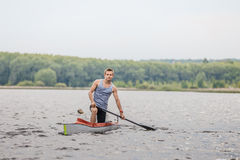 Athlete canoeist with an oar in a canoe after finish Royalty Free Stock Photos