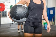 Athlete Carrying Medicine Ball At Gym. Midsection of female athlete carrying medicine ball at gym Royalty Free Stock Image