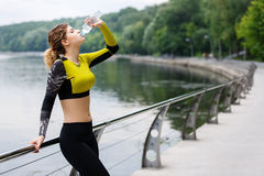 Athlete caucasian woman in sportswear drinking water after sport Stock Images