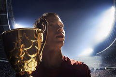 Athlete cheering with trophy cup at night Stock Images