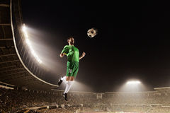 Athlete chesting soccer ball in stadium at night. Athlete chesting soccer ball in stadium royalty free stock photography