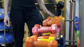 The athlete chooses dumbbells from a large set of inventory to load. Person in a black dress is suitable for equipment of different colors, first selects stock video footage