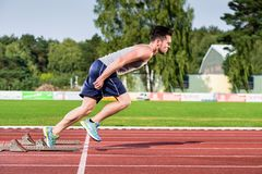 Athlete on cinder track of sports facility starts to sprint Stock Photography