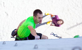 Athlete on climbing Wall and belaying referee watching him. Male Athlete moving up on vertical climbing Wall and his belaying Partner staying on Background Royalty Free Stock Images