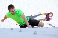 Athlete on climbing Wall and belaying referee watching him. Male Athlete moving up on vertical climbing Wall and his belaying Partner staying on Background Royalty Free Stock Photo