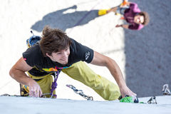 Athlete on climbing Wall and belaying referee watching him. Male Athlete moving up on vertical climbing Wall and his belaying Partner staying on Background Stock Images
