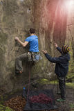 Athlete climbs on rock with rope. Stock Photos