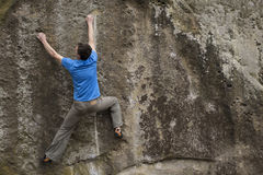 Athlete climbs on rock with rope. Royalty Free Stock Images