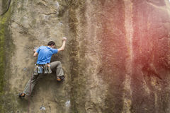Athlete climbs on rock with rope. Stock Photography