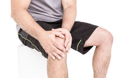 Athlete clutching knee in excruciating pain. On white background Royalty Free Stock Photos