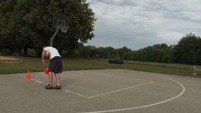 Athlete collects orange cones from the basketball court. In summer day stock footage