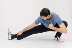Athlete crouching pulling muscles of the right leg Stock Image