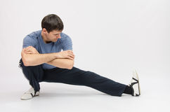 Athlete crouching stretches muscles of left leg Stock Image