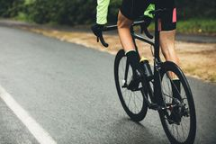 Athlete cycling on country road. Male athlete cycling on country road. Cropped shot of man riding bicycle on wet road, practicing for a competition Stock Image