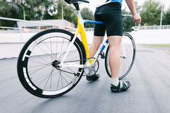 An athlete cyclist is standing with a bright bike background architecture. Bicycle close up. Royalty Free Stock Images