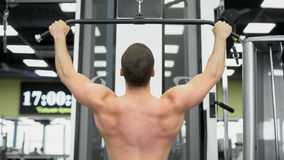 The athlete does exercises for the muscles of the back. Muscular back of the bodybuilder on block device in the gym royalty free stock photography