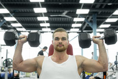 Athlete doing exercise for shoulders with dumbbells sitting on a bench. young muscular man trains at the gym. Athlete doing exercise for shoulders with Royalty Free Stock Image