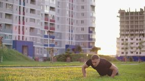 An athlete doing extreme push up at Superman using backflips and pushups at sunset in slow motionon the background of. An athlete doing extreme push up at stock footage
