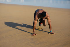 Athlete doing mountain climbers hiit workout. Fit man warming up before running at the beach. Black athlete on hiit cardio outdoor workout. Mountain climbers Royalty Free Stock Photo