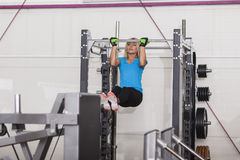 Bodybuilding. Strong fit woman exercising in a gym - doing pull-ups. Athlete doing pull-up on on a crossbeam - horizontal bar. Female fitness in gym royalty free stock photography