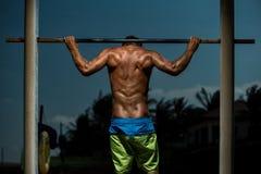 Athlete doing pull-up on horizontal bar Stock Photo