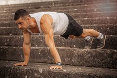 Athlete is doing a push up. Young, muscular athlete is doing a push up outdoor Royalty Free Stock Photography