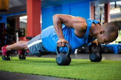 Athlete doing push-ups with kettlebells. Full length of male athlete doing push-ups with kettlebells in fitness studio royalty free stock photography