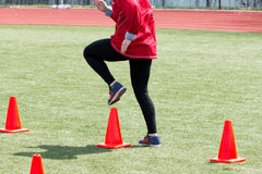 Athlete doing running drills over cones. A track and field athlete does speed form drills over orange cones on a green turf field stock photography