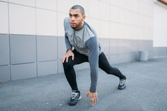 Athlete doing stretching exercise before running. Jogger on morning fitness workout. Runner in sportswear on training outdoor Stock Photo