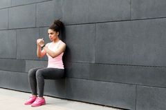 Athlete doing wall squat. On city street stock image