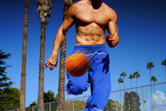 Athlete dribbling basketball. Young athlete dribbling basketball outdoors while running royalty free stock photos
