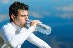 Athlete drinking. Handsome sportman drinking water on a break with water reflections in background Stock Image