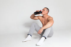 Athlete drinking from a shaker Royalty Free Stock Photos