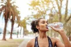 Athlete drinking water during morning jog. Woman runner drinking water from a bottle during workout. Female athlete taking a break from her workout Stock Photography
