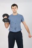 Athlete with a dumbbell effort raises his right hand Royalty Free Stock Image