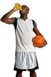 Athlete With Energy Drink. An attractive athletic man with a basketball drinking an energy drink against white background Royalty Free Stock Images