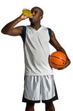 Athlete With Energy Drink. An attractive athletic man with a basketball drinking an energy drink against white background Royalty Free Stock Photography