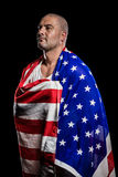 Athlete with england flag wrapped around his body. Athlete posing with england flag wrapped around his body on black background Stock Photo
