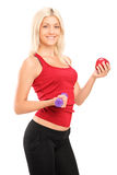 Athlete female holding a dumbbell and apple Royalty Free Stock Photos