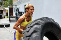 Athlete female working out with a huge tire, turning and flippin Royalty Free Stock Photos