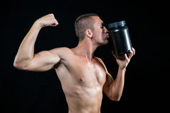 Athlete flexing muscles while kissing container. Shirtless athlete flexing muscles while kissing nutritional supplement container against black baackground Stock Photo