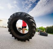 Athlete Flipping Large Tire Royalty Free Stock Images