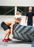 Athlete Flippng Tractor Tire Stock Images