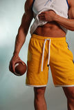 Athlete with Football. Muscular male athlete in Yellow workout shorts with white drawstring holding a football Royalty Free Stock Images