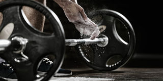 Athlete getting ready for weight lifting training. Sports background. Young athlete getting ready for weight lifting training. Powerlifter hand in talc royalty free stock photography